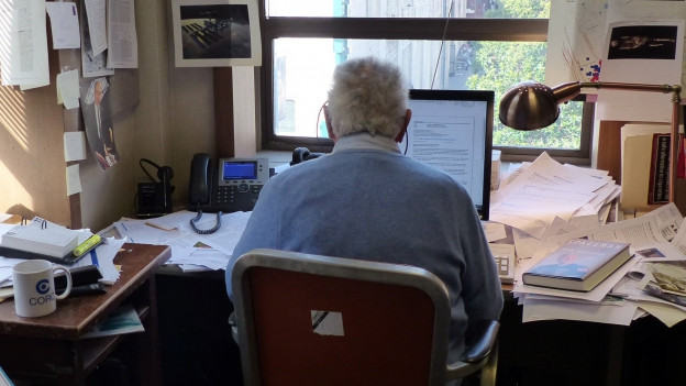 David Perlman sitzt an seinem Bürotisch, um ihn herum liegen Berge von Büchern und Dokumente.