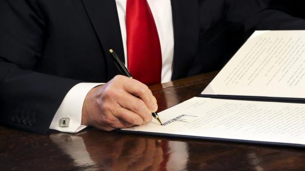 Nahaufnahme von Trumps Hand, die ein Dokument unterschreibt.