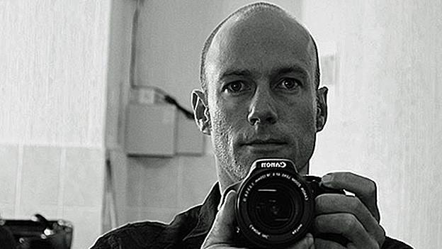 Samuel Schlaefli. Portraitbild mit Kamera.