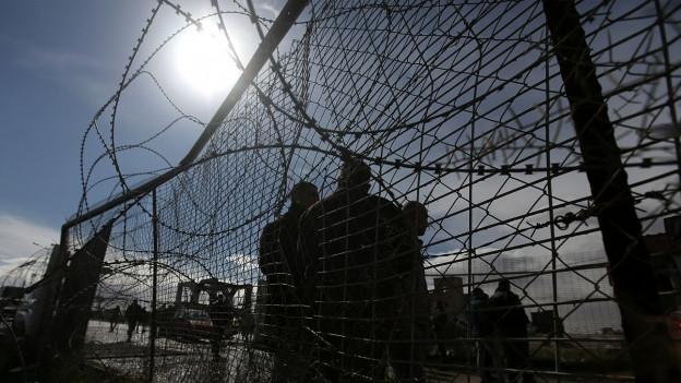 Drei Männer stehen hinter einem Stacheldrahtzaun im Gaza-Streifen.