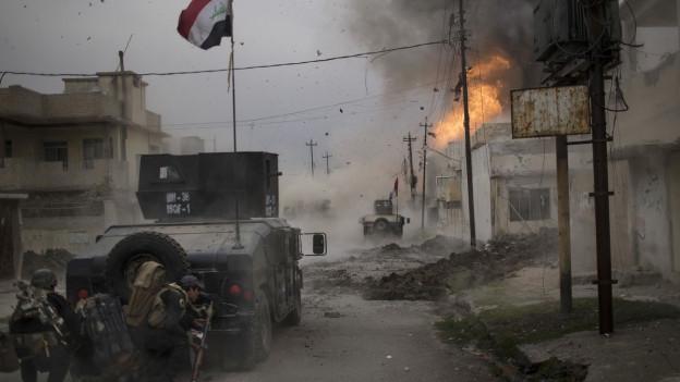 Irakische Soldaten positionieren sich hinter einem Panzer in Mosul.