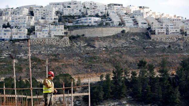 Israel treibt den Bau jüdischer Siedlungen im besetzten Ostteil Jerusalems wieder voran. Ein Arbeiter auf einer Baustelle in der israelischen Siedlung von Ramot, im Hintergrund die Siedlung von Ramat Shlomo.