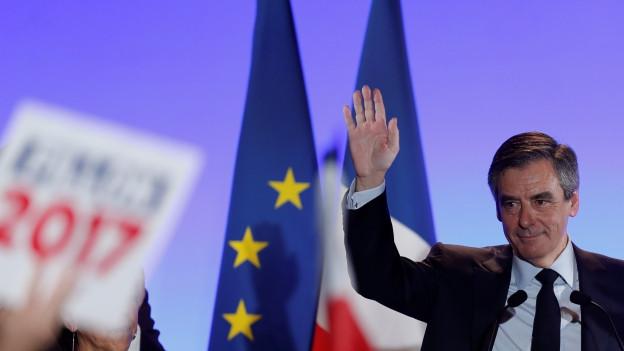 Fillon winkt vom Rednerpult, links ein Wahlkampftransparent