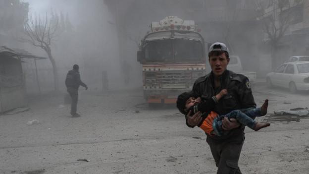 Ein Mann trägt ein Kind in Ost-Ghouta.
