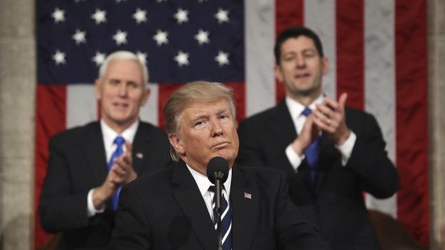 Drei Männer; einer sitzend im Vordergund, zwei klatschend dahinter.