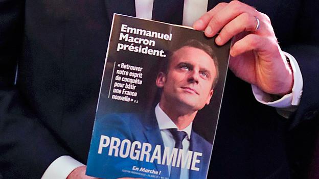 Zwei Hände halten das Wahlkampfprogramm von Emmanuel Macron.