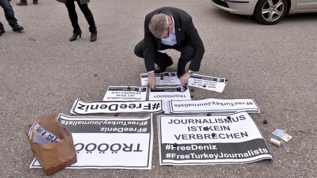 Ein Mann legt Protestschilder auf eine Strasse, auf denen «Journalismus ist kein Verbrechen» und «#FreeDeniz» steht.