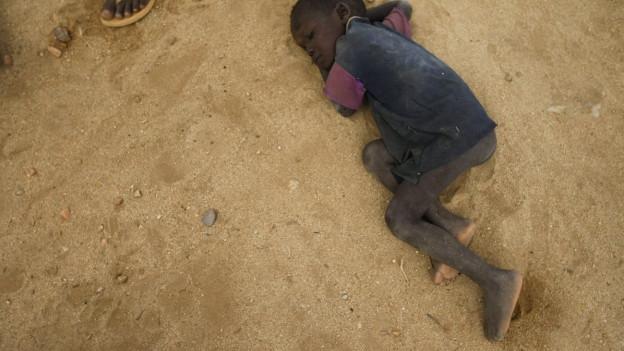 Ein kleiner Junge liegt auf dem sandigen Boden, in der Nähe des Flüchtlingslagers Kakuma.