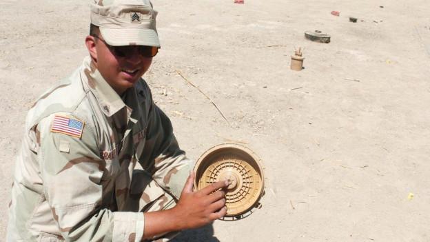 Ein amerikanischer Soldat zeigt eine Landmine im Irak.