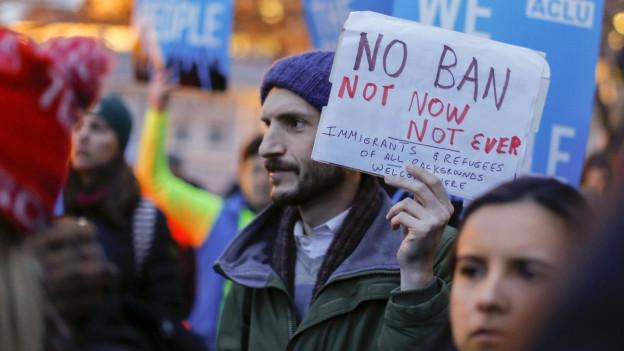 Demonstranten gehen gegen das erneute Einreiseverbot auf die Strasse.