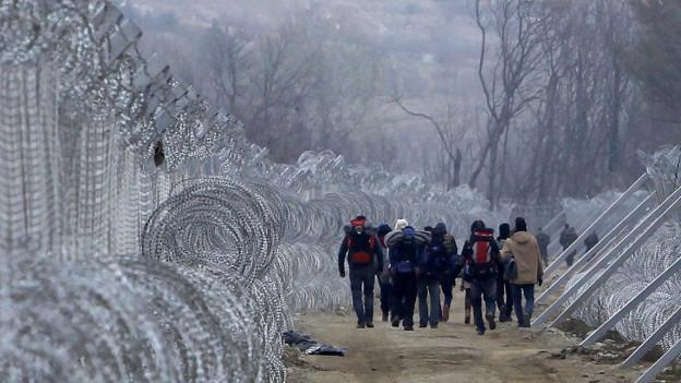 Flüchtlinge zwischen den beiden Grenzzäunen an der griechisch-mazedonischen Grenze.