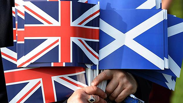 Britische und schottische Papierfähnchen werden von einer Hand gehalten.