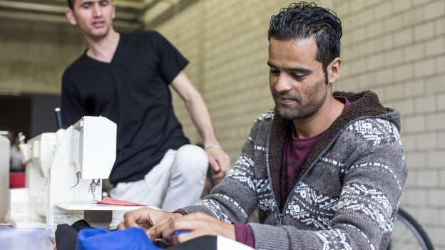 Ein afghanischer Flüchtling übt das Nähen mit der Nähmaschine.