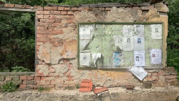 Zu sehen ist eine menschenleere Strasse im Dorf Protop, wo nur noch Todesanzeigen ausgehängt werden.
