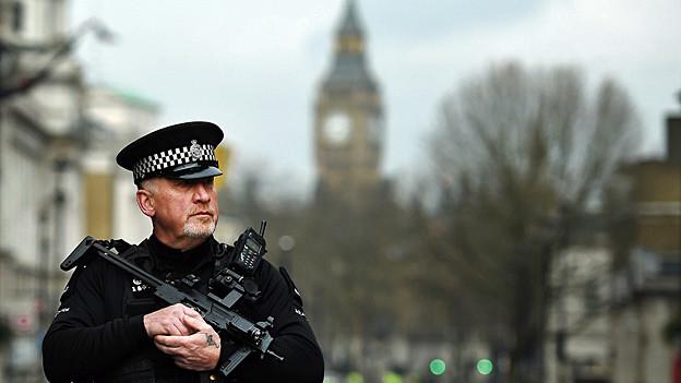 Ein bewaffneter Polizist steht in einer Strasse im Zentrum von London.