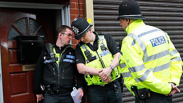 Polizeioffiziere stehen vor einem Haus.