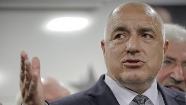 Boiko Borisov, im dunklen Anzug und mit Glatze, die rechte Hand erhoben.