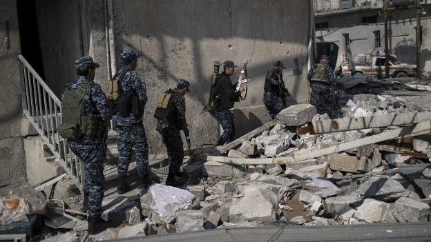 Soldaten in der irakischen Stadt Mossul vor einem zerbombten Haus.