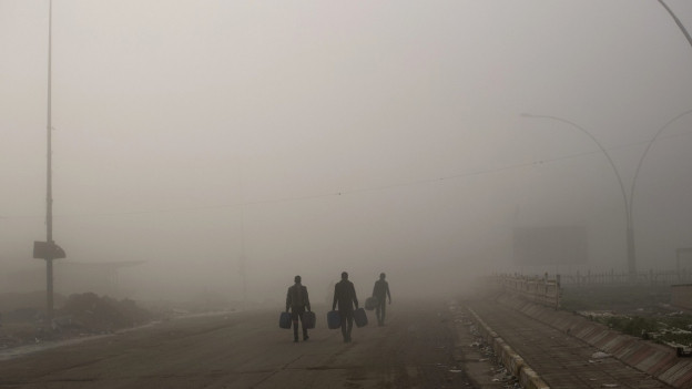 Zu sehen sind drei Zivilisten, die über eine staubige Strasse in Mossul, Irak, gehen.
