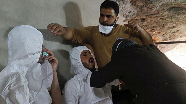 Hilfskräfte in weissen Schutzanzügen atmen durch Sauerstoffmasken.