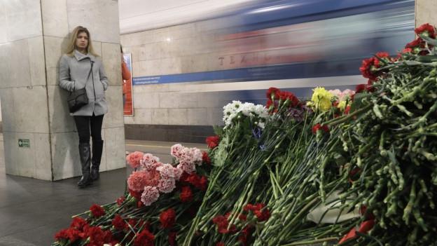 In einer U-Bahnstation in St. Petersburg liegen Blumen am Boden, eine Frau sieht sich die Blumen an, eine U-Bahn fährt vorbei.