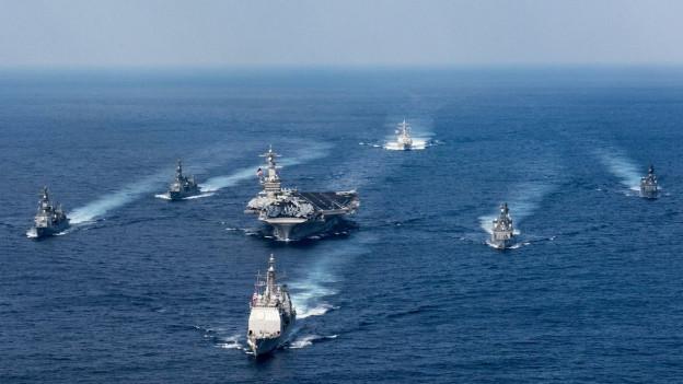 Ein US-Flugzeugträger umringt von Eskortschiffen unterwegs auf offener See Korea.