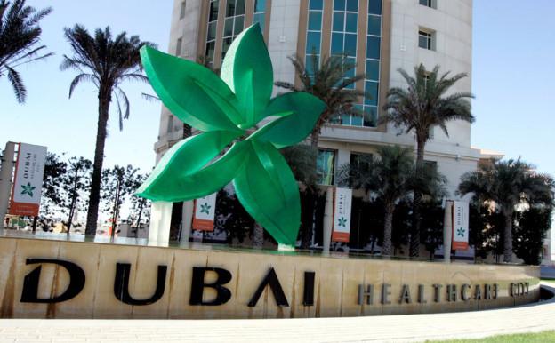 Einige Gebäude, darunter steht auf einer Mauer «Dubai Healthcare Center».