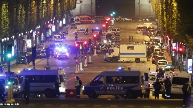 Die Champs-Elysées in der Nacht: viel Polizei und Autos, eine Strassensperre.