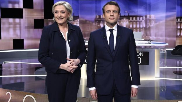 Marine Le Pen und Emmanuel Macron stehen im Fernsehstudio nebeneinander und lächeln für die Kameras.
