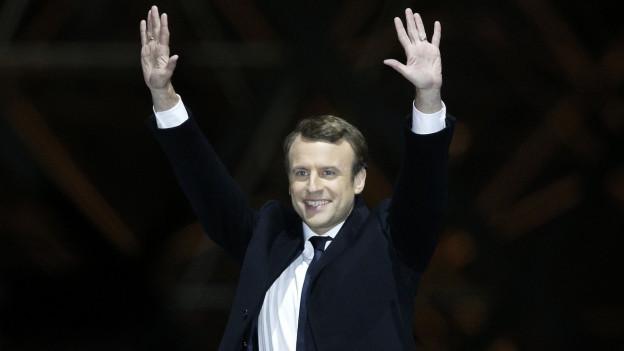 Emmanuel Macron feiert seine Wahl vor dem Louvre in Paris, beide Arme in Siegerpose in die Luft gestreckt, im schwarzen Anzug.