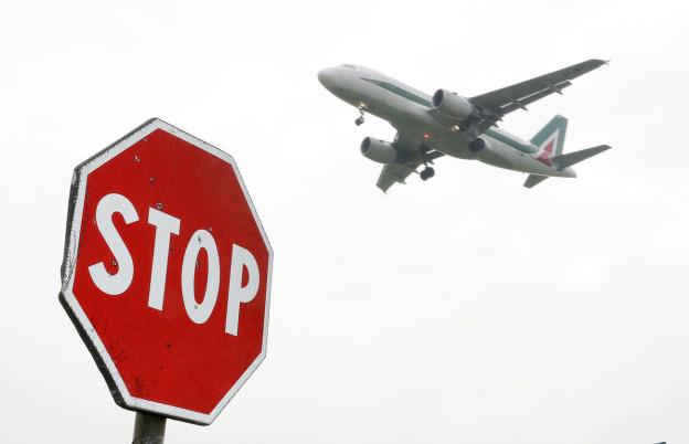 Im Vordergrund ein Schild mit der Aufschrift «Stopp», im Hintergrund ein Flugzeug im Abflug.