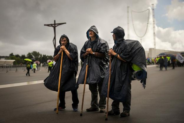 Das Bild zeigt drei Pilger mit Gehstöcken im portugiesischen Fátima im Mai 2017.