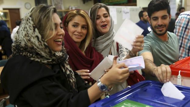 lachende Frauen und ein Mann stecken Stimmzettel in Wahlurne.