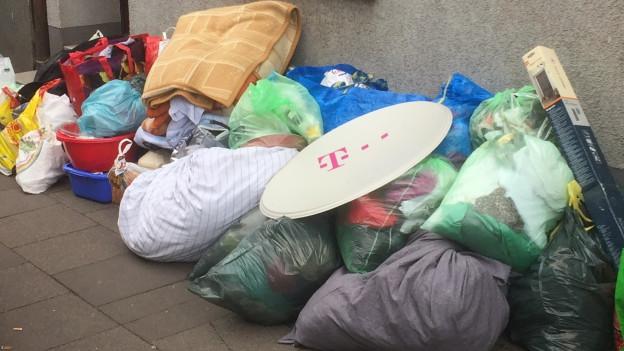 Durchsichtige Plastiksäcke stapeln sich auf dem Gehsteig. Darin sind die Habseligkeiten der Roma verpackt.