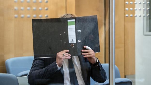 Ein Zeuge in Deutschland bedeckt im Gerichtssaal sein Gesicht mit einem Ordner.
