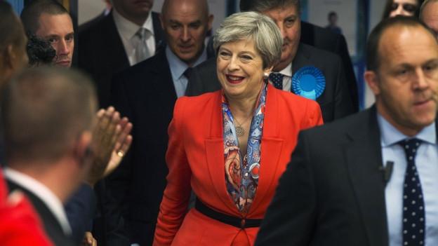 Die lachende Theresa May im knallroten Anzug inmitten einer Menge von Männern in dunklen Anzügen.