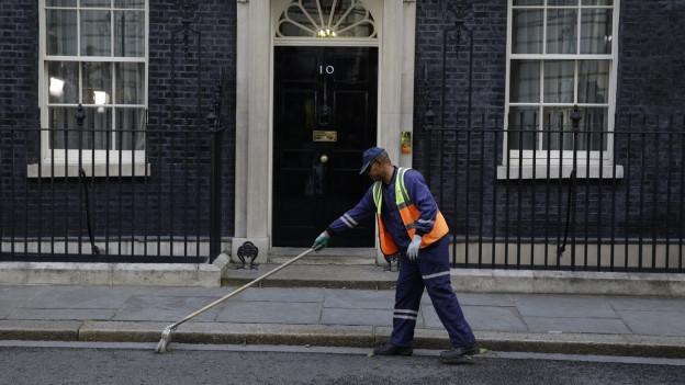 Ein Strassenfeger wischt vor der Residenz der Premierministerin in London.