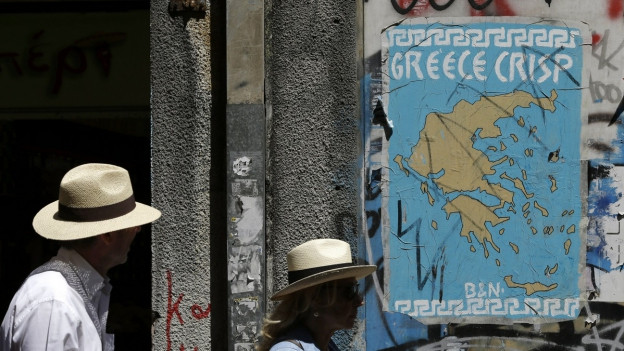 Fussgänger gehen in Athen an einem Plakat mit den Umrissen Griechenlands vorbei, im Schriftzug wurde der Buchstabe E mit dem Eurosymbol ersetzt.