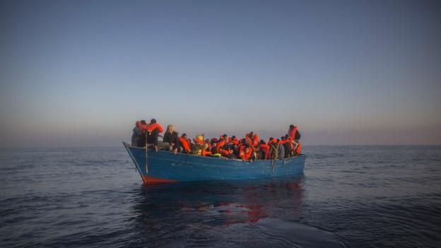 Flüchtlinge und Migranten aus Afrika und Asien, dicht gedrängt auf einem Boot, warten vor der Küste Libyens auf die Hilfe einer Nichtregierungsorganisation.