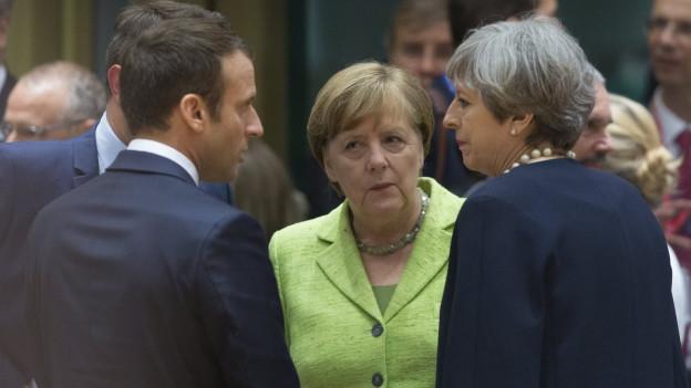 Theresa May, Angela Merkel und Emmanuel Macron reden miteinander.
