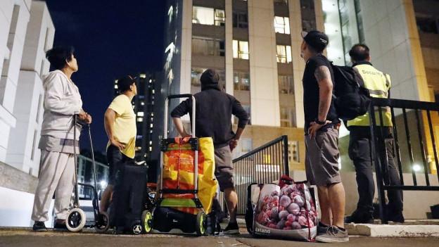 Bewohner mit Gepäckstücken blicken zum Hochhaus empor, das sie verlassen mussten.