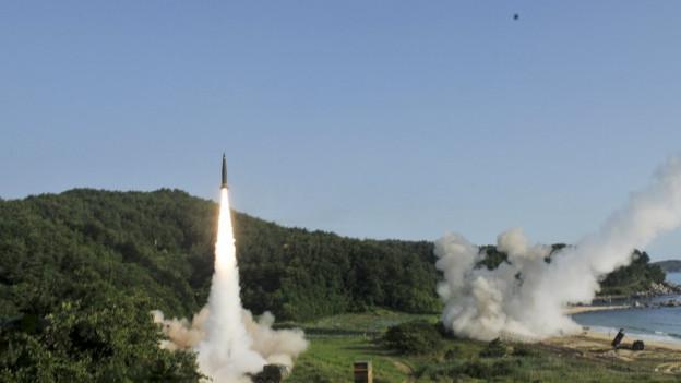 Eine Rakete steigt an der südkoreanischen Küste in die Luft, unter ihr ein Schweif aus dichtem Rauch, im Hintergrund begrünte Hügel.