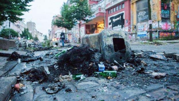 Nach den gewalttätigen Demonstrationen in Hamburg liegen am Morgen Trümmer und Dreck in den Strassen, zum Beispiel ein kaputtes Velo und abgebrannte Mülleimer.