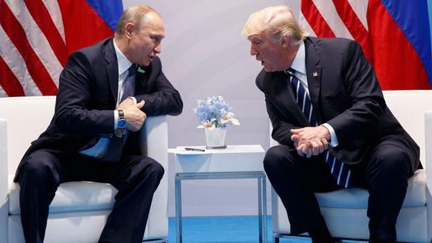 Wladimir Putin und Donald Trump unterhalten sich bei einem Treffen.