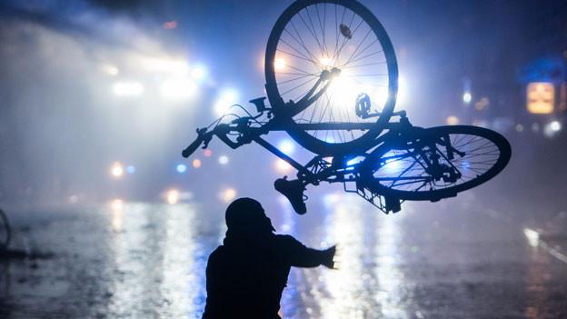 Ein Randalierer wirft am 09.07.2017 in Hamburg im Schanzenviertel ein Fahrrad in Richtung von Wasserwerfern.