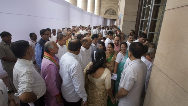 Eine Personenschlange vor einem Wahllokal in Indien