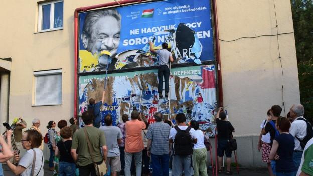 Aktivisten zerreissen ein Plakat auf dem der ungarisch-amerikanische Milliardär und Jude George Soros schlecht gemacht wird.