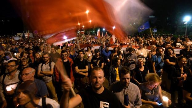 Das Bild zeigt vornehmend Jugendliche, die in den Strassen Warschaus mit Kerzen gegen die umstrittene Justizreform demonstrieren.
