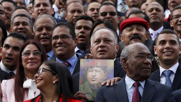 Zu sehen sind die Mitglieder der verfassungsgebenden Versammlung, die ein Bild von Hugo Chavez.