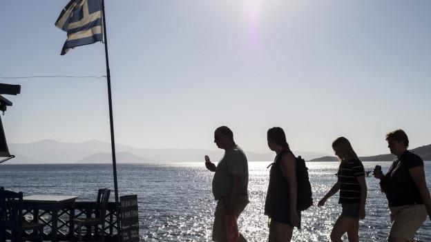 Vier Touristen laufen am Meer entlang neben Griechenland-Fahne vorbei.